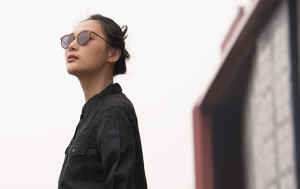 Woman in sunglasses looking up