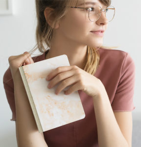 Girl wearing metal eyeglasses with book