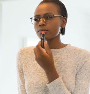 Woman applying lipstick wearing glasses