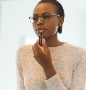 Woman applying lipstick wearing glasses