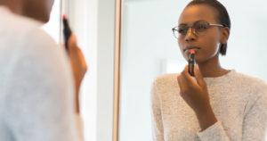 Woman wearing glasses applying lipstick