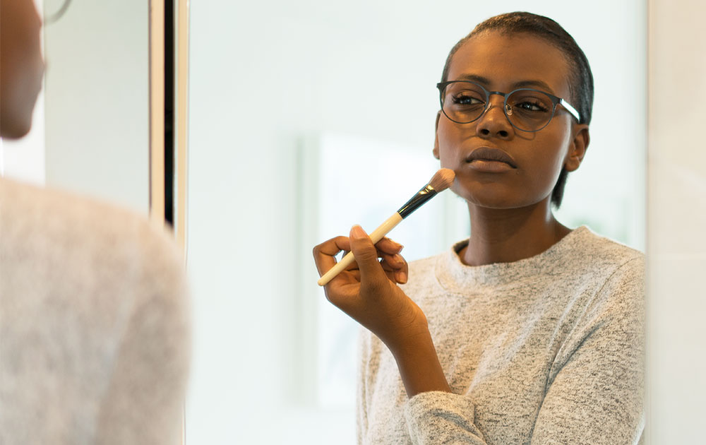 Woman wearing glasses with makeup brush