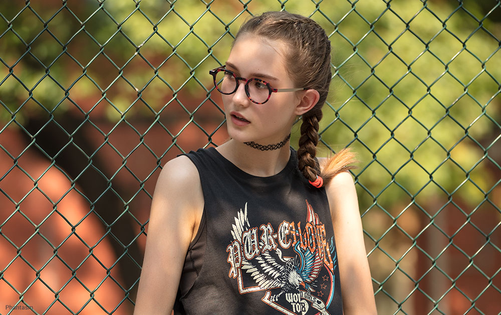 Girl wearing glasses against a fence