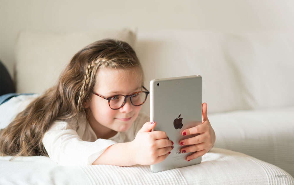 Girl - glasses - tablet - bed