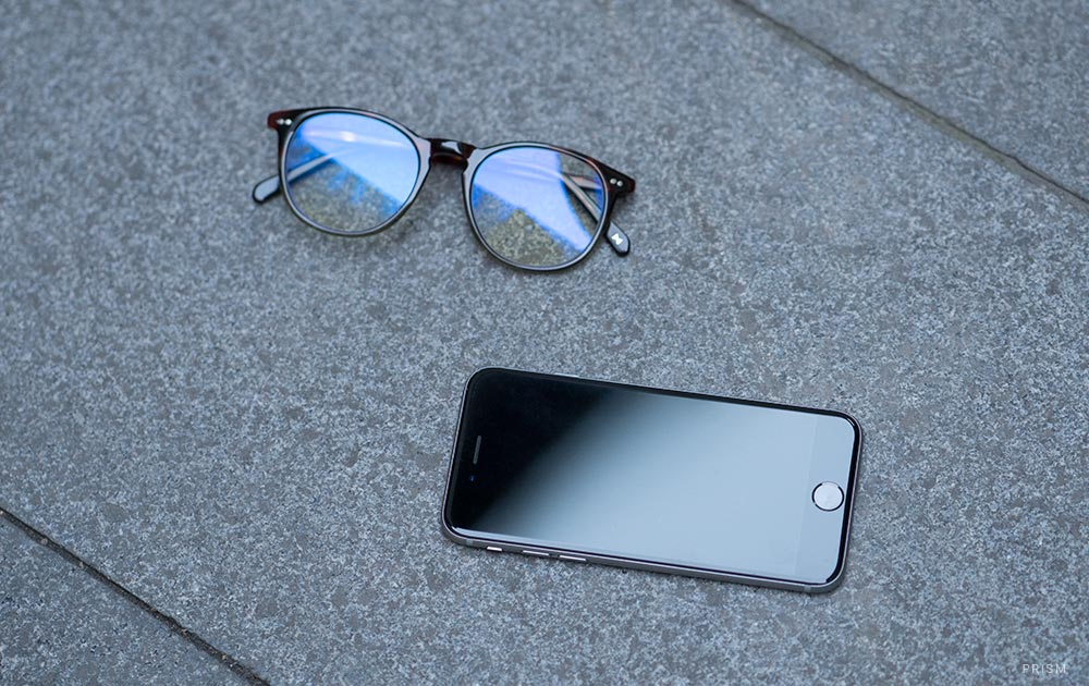Blue light blocking glasses next to a mobile phone