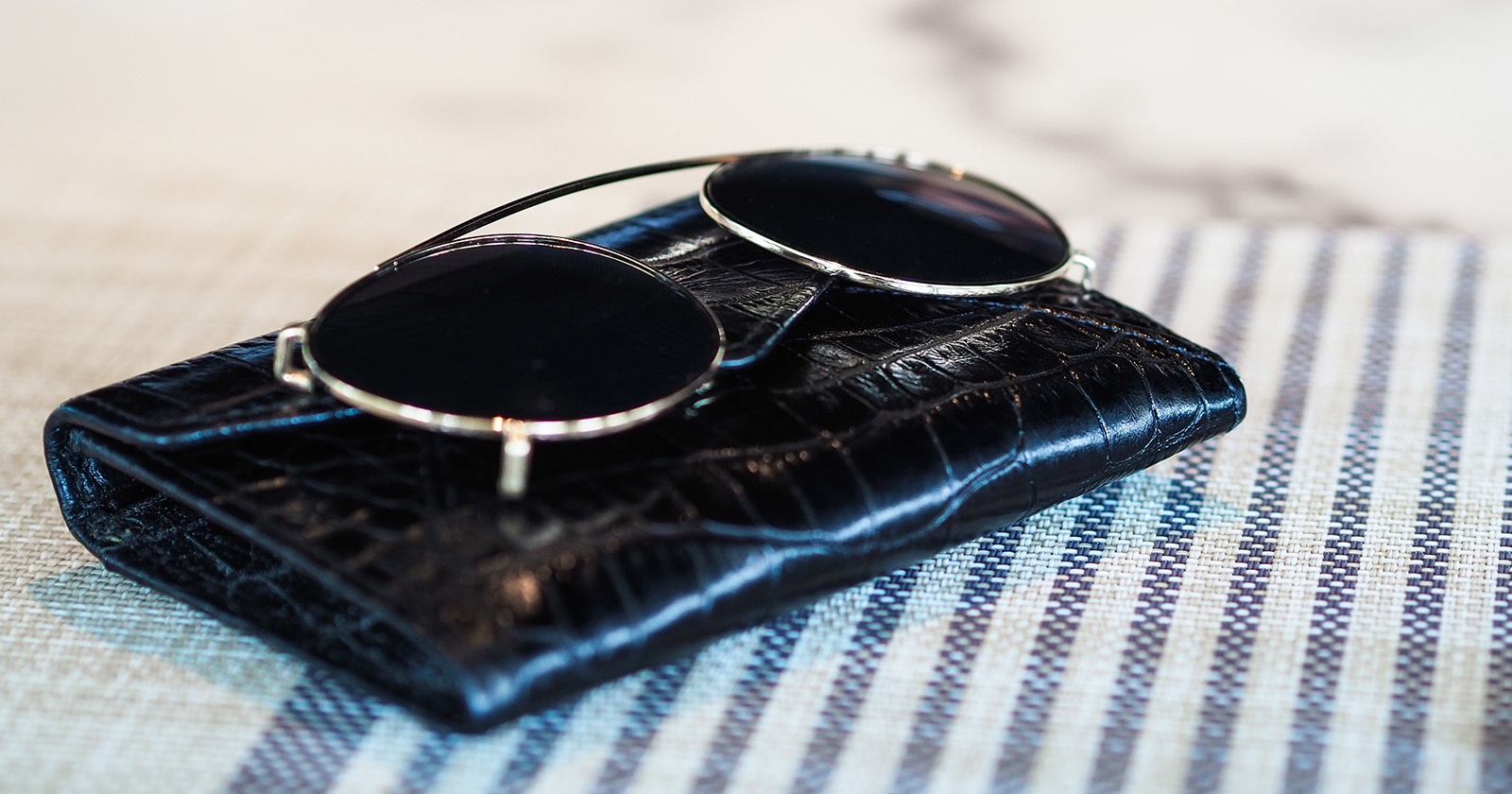 A set of clip-on sunglasses on a black case