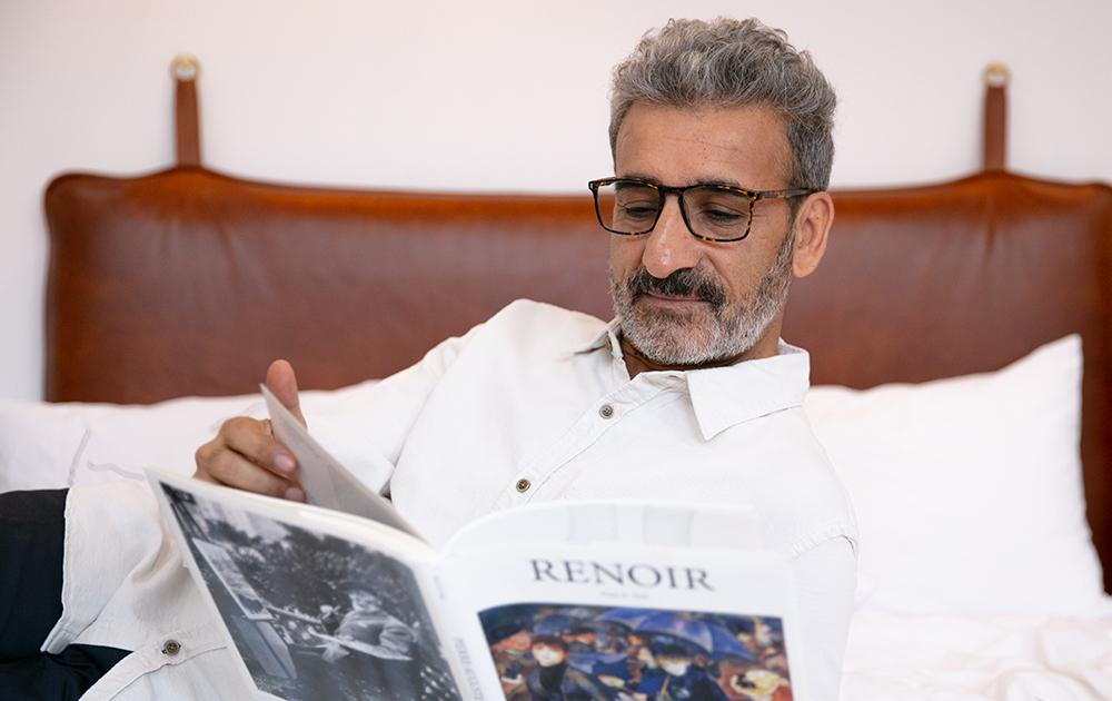 A man wearing tortoiseshell reading glasses reading a book